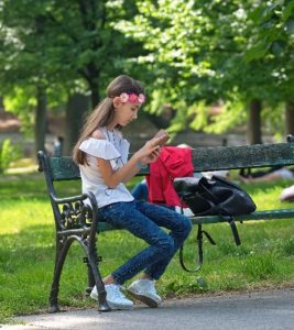 Child sitting on a bench looking at smartphoneq